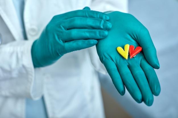 Doutor, segurando os símbolos do coração na mão com o conceito de assistência médica, medicina no hospital, cardiologia