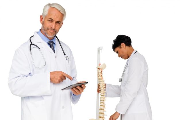 Doutor, segurando, tabela digital, com, colega, por, esqueleto, modelo