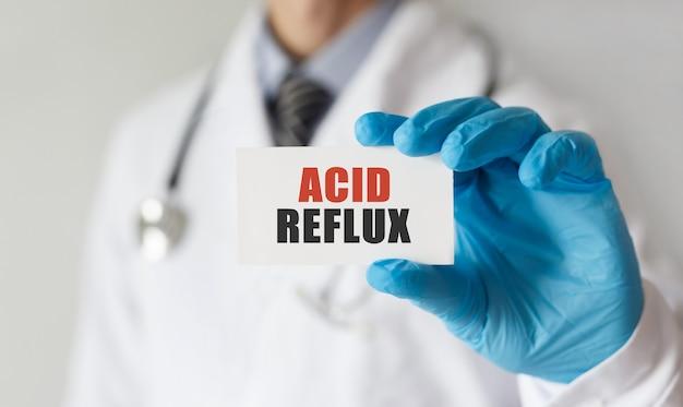Doutor segurando um cartão com o texto acid reflux, conceito médico