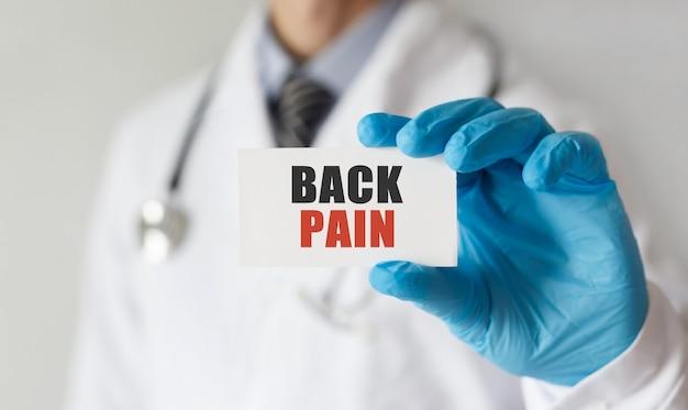 Doutor segurando um cartão com o texto back dor, conceito médico