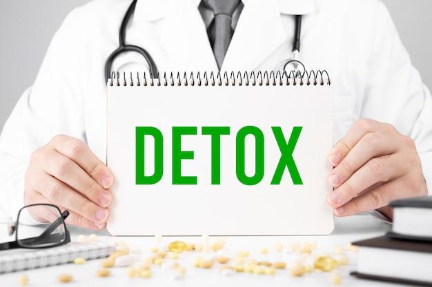 Doutor, segurando um cartão com o texto detox, conceito médico