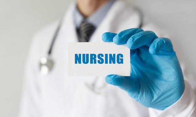 Doutor, segurando um cartão com o texto enfermagem, conceito médico