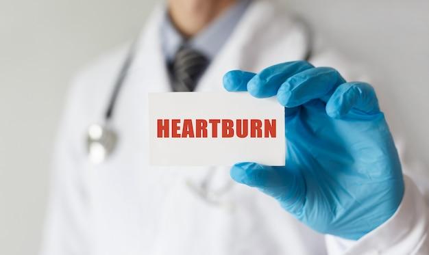 Doutor segurando um cartão com o texto heartburn, conceito médico