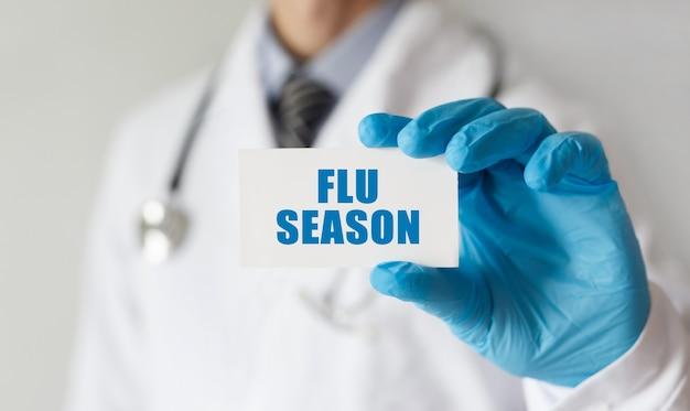 Doutor, segurando um cartão com o texto temporada de gripe, conceito médico