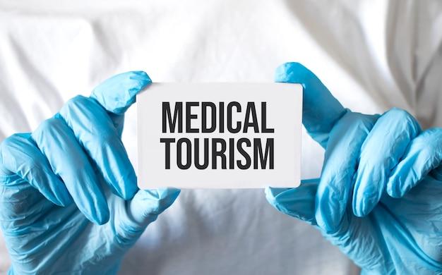 Doutor, segurando um cartão com o texto turismo médico, conceito médico