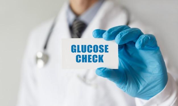 Doutor segurando um cartão com o texto verificação de glicose, conceito médico