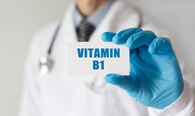 Doutor segurando um cartão com o texto vitamina b1, conceito médico