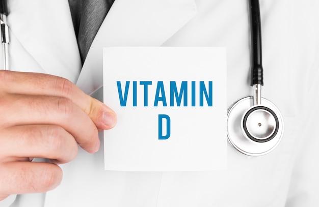Doutor segurando um cartão com o texto vitamina d, conceito médico