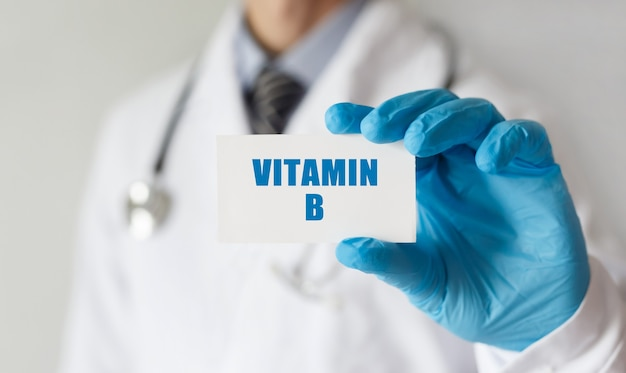 Doutor segurando um cartão com texto vitamina b, conceito médico