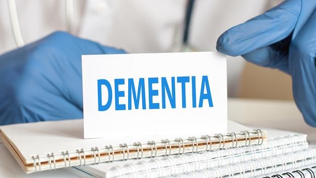 Doutor, segurando um cartão de papel branco com o texto: demência. conceitos de saúde para hospitais, clínicas e negócios médicos.