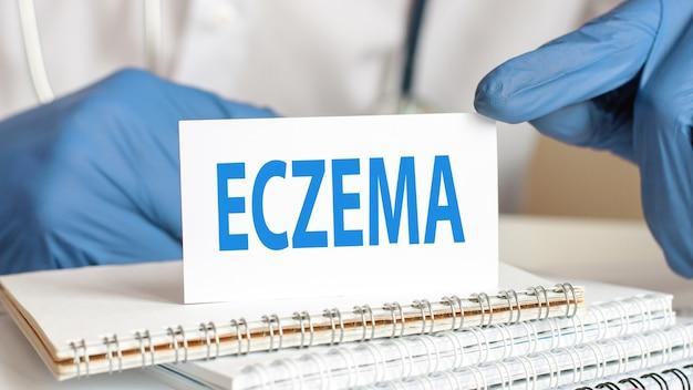 Doutor, segurando um cartão de papel branco com o texto: eczema. conceitos de saúde para hospitais, clínicas e empresas médicas.