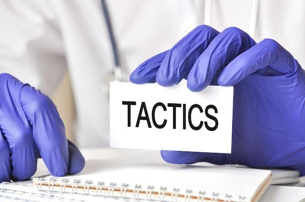 Doutor, segurando um cartão de papel branco com texto: táticas. conceitos de saúde para hospitais, clínicas e negócios médicos.