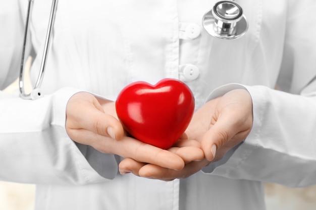 Doutor segurando um coração de plástico nas mãos, closeup