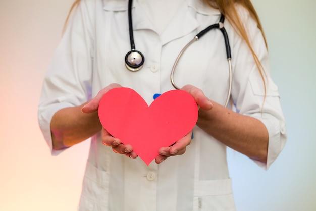 Doutor, segurando um coração vermelho. cardiologista com formato de coração nas mãos fechar