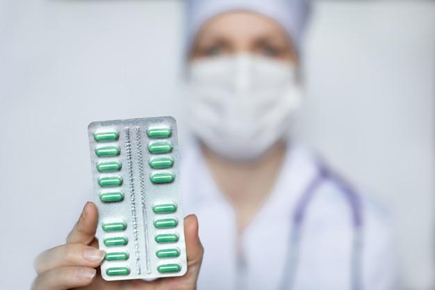 Doutor, segurando um pacote de close-up de comprimidos verdes.