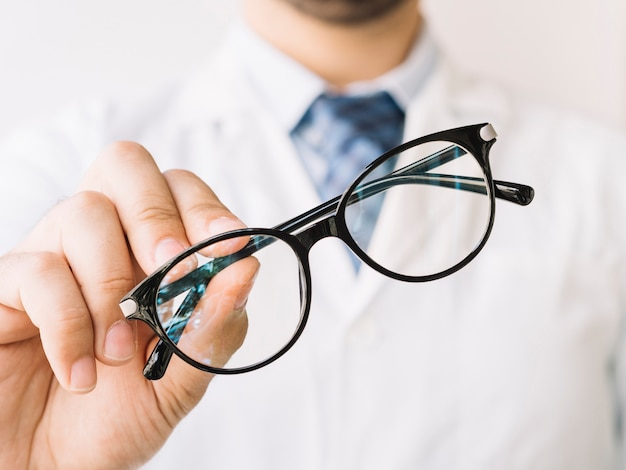 Doutor, segurando um par de óculos emoldurados pretos