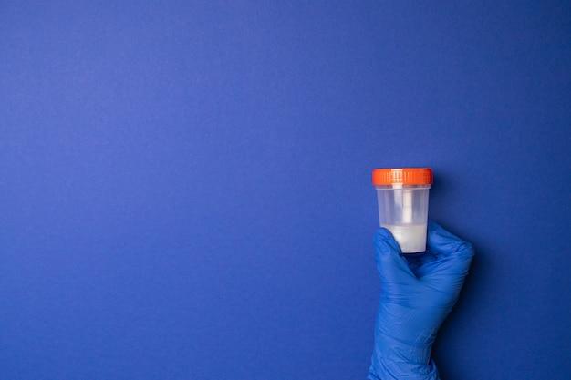 Doutor, segurando um recipiente de plástico com esperma para análise médica. inseminação artificial
