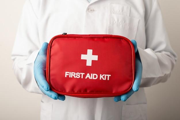 Doutor, segurando uma caixa vermelha com o kit de primeiros socorros de inscrição. conceito de sistema de saúde, tratamento
