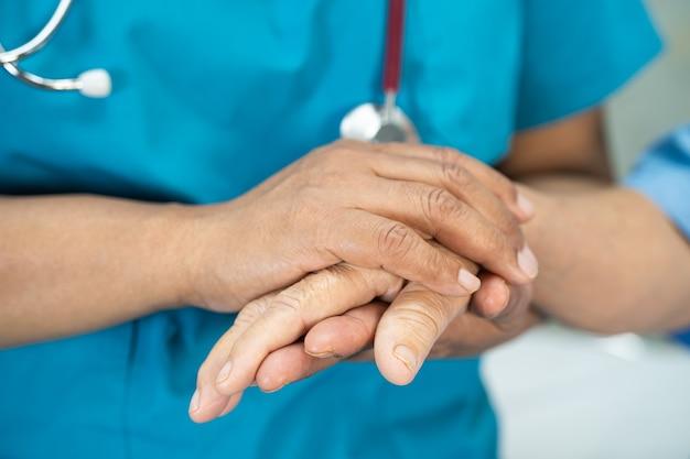 Doutor, segurando uma paciente asiática sênior com amor.