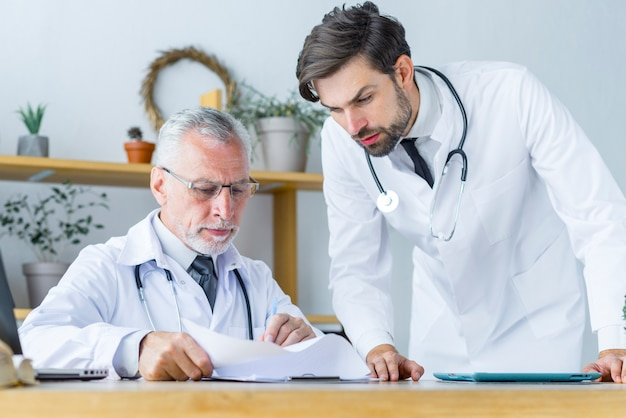 Doutor sênior, mostrando, papeis, para, jovem, colega
