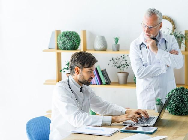 Doutor sênior, olhar, jovem, colega, usando computador portátil