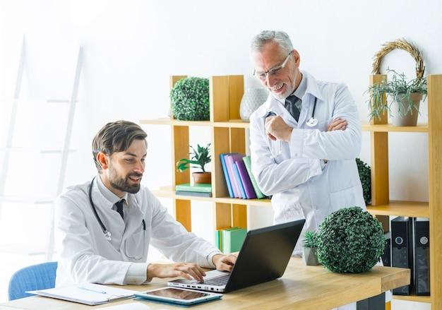 Doutor sênior, olhar, trabalhando, colega