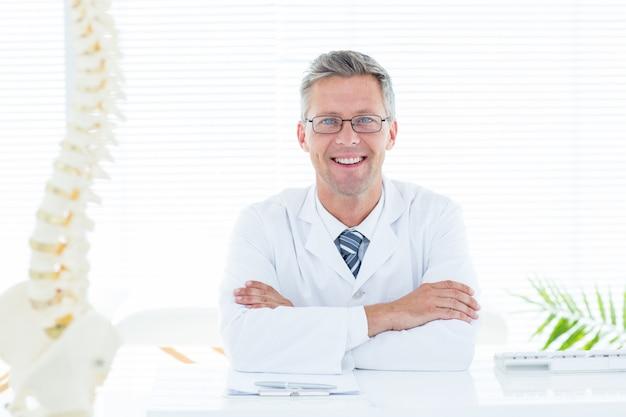 Doutor, sentando, em, seu, escrivaninha, sorrindo, câmera
