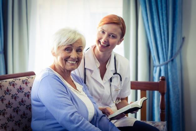 Doutor sorridente, ajudando a mulher sênior a ler um livro