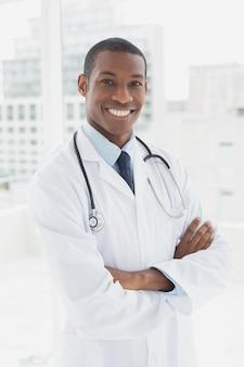 Doutor sorridente com braços cruzados em um consultório médico