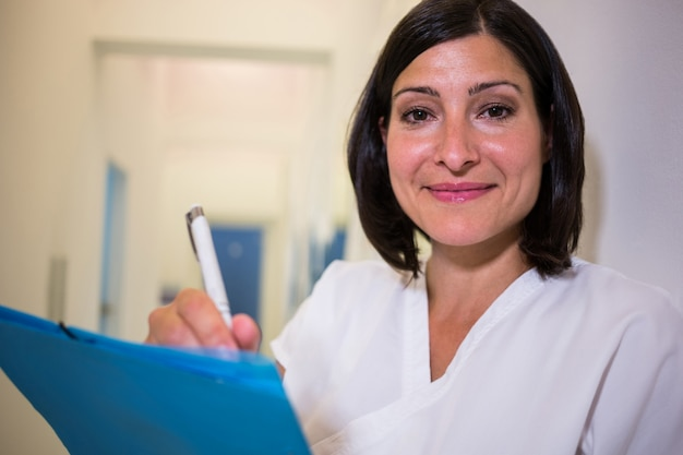 Doutor sorridente, examinando o relatório de pacientes