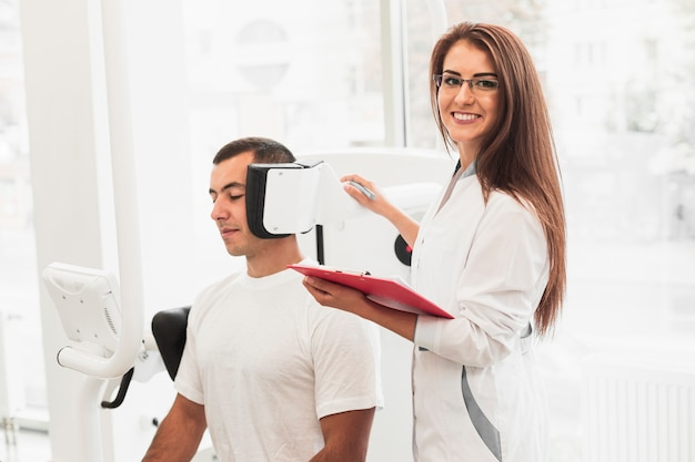 Doutor sorridente segurando a área de transferência, verificando o paciente