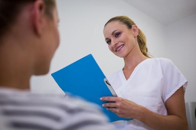 Doutor sorridente segurando relatórios médicos