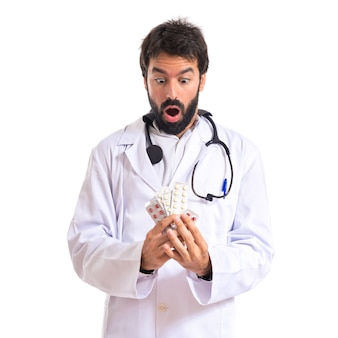 Doutor surpreso segurando pílulas sobre fundo branco