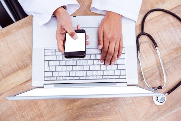 Doutor, usando, smartphone, madeira, escrivaninha