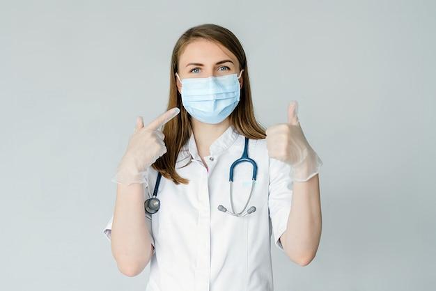 Doutor wearing medical mask e luvas isoladas mostrando na máscara e no polegar acima. preventivas contra o conceito de vírus