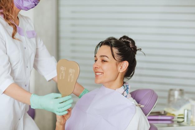 Doutora dentista atraente loira na máscara médica e luvas posando com paciente do sexo feminino morena segurando o espelho e sorrindo.
