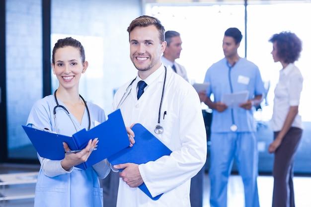 Doutores, com, relatório médico, olhar, e, sorrindo, em, hospitalar