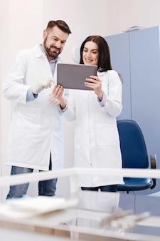 Doutores felizes, positivos e simpáticos, juntos e sorrindo enquanto olham para a tela do tablet