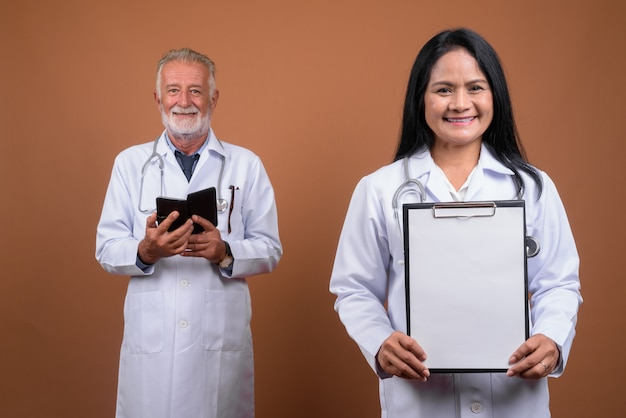 Doutores maduros multi-étnica dos pares no marrom
