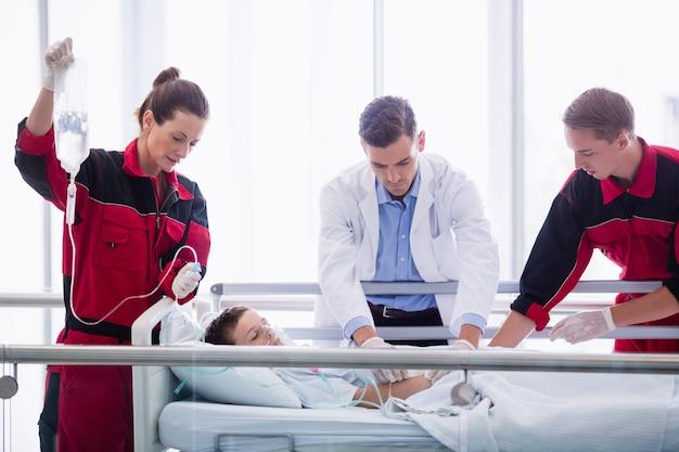Doutores que examinam paciente no corredor