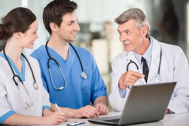 Doutores trabalhando juntos em um laptop no consultório médico.