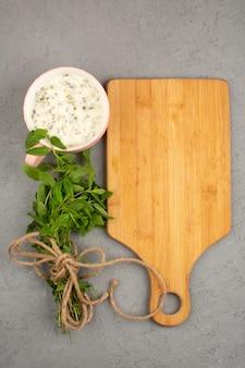 Dovga com ervas ao longo da mesa de madeira marrom sobre um piso claro