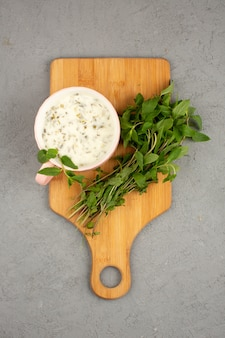 Dovga fresco com verduras dentro, juntamente com ervas verdes frescas ao redor em um brilhante
