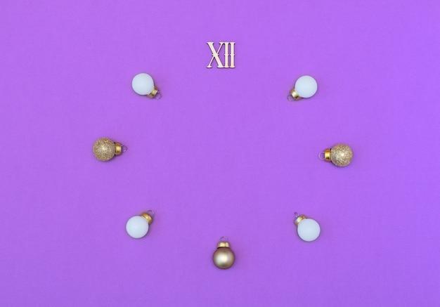 Doze números romanos com bolas de natal brancas e douradas na forma de um relógio sobre fundo roxo.