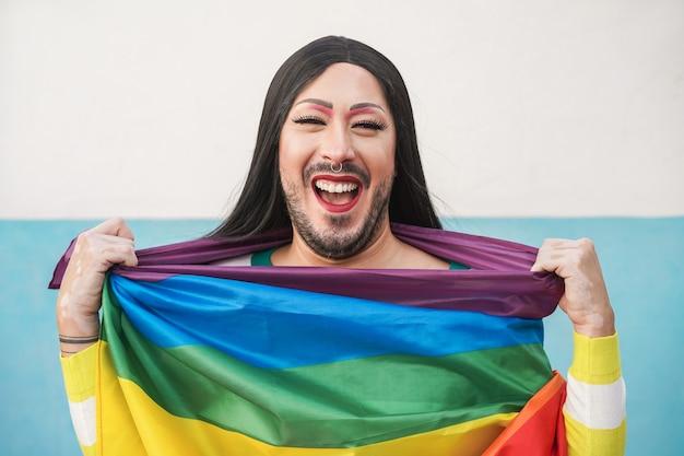 Drag queen feliz usando a bandeira do arco-íris