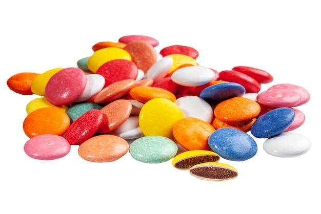 Drageias de chocolate em esmalte de açúcar multicolorido isolado no branco