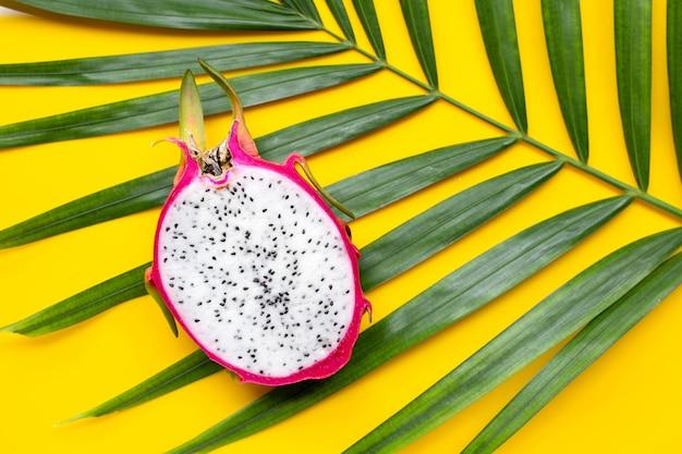Dragonfruit maduro ou pitaya em folhas de palmeira tropical.