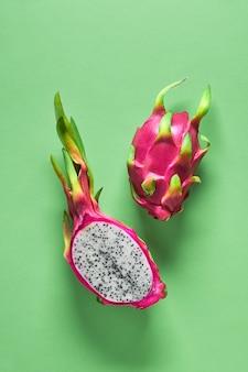 Dragonfruit orgânico fresco cortado ao meio no fundo verde vibrante hortelã na moda. layout plano criativo com frutas exóticas da moda nas cores rosa e verdes em negrito.