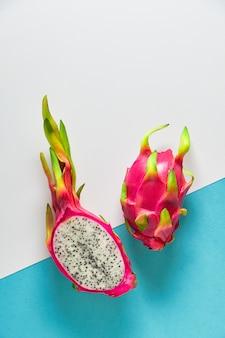 Dragonfruit orgânico fresco (pitaya ou pitaiaiás) cortado ao meio na hortelã azul rachada de dois tons e na parede branca. layout plano criativo com frutas exóticas da moda em cores vibrantes em rosa e verde.