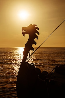 Drakkar viking em mar aberto ao pôr do sol